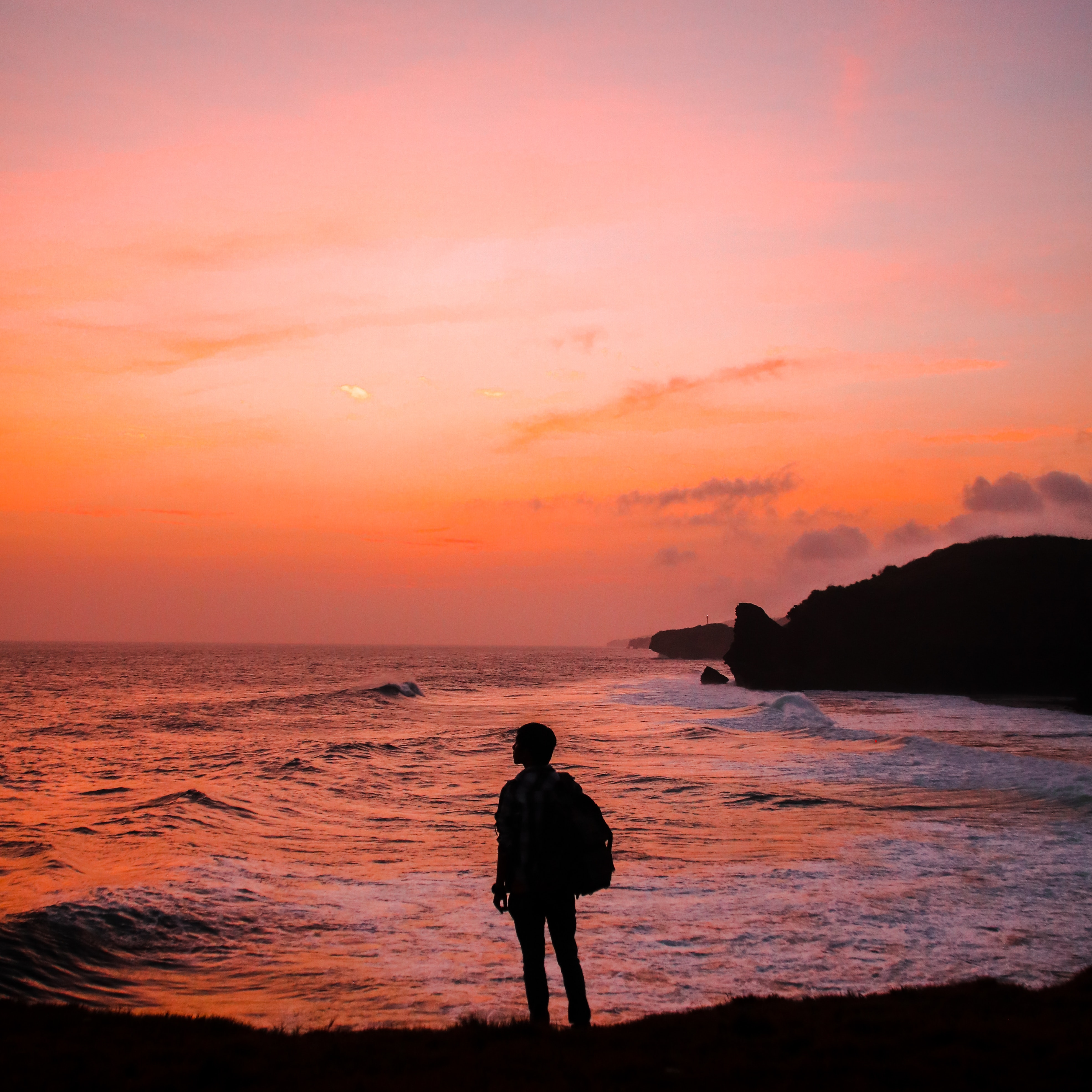 silhouette-photo-of-man-with-backpack-standing-in-seashore-848573